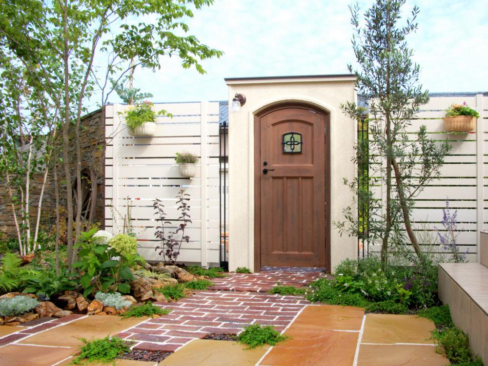 植物の緑が映える白いフェンスと自然石の敷石が可憐な風景を作ります。