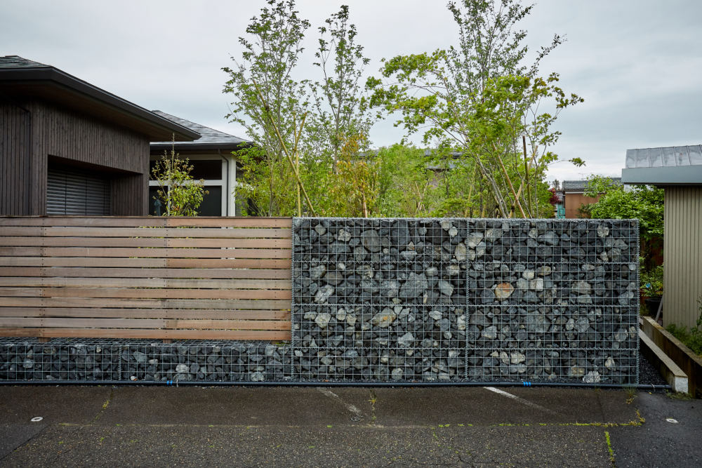 高木の庭を囲むのはロックウォールとハードウッドのフェンス。 ハードウッドは時間の経過と共にシルバーグレー色へと変化し、更にロックウォールと相性のよい色合いに。