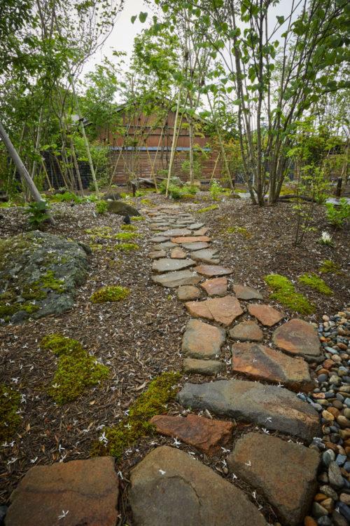なだらかな傾斜を付けた自然石のアプローチは木立を縫って鉄平石の石張りまで続きます。