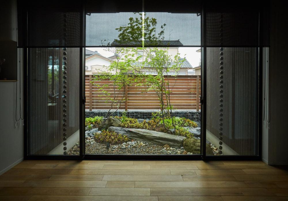 雑木林のような庭を抜けて玄関を開けると現れる額縁のような坪庭。 景石と高木のバランスが美しい庭です。