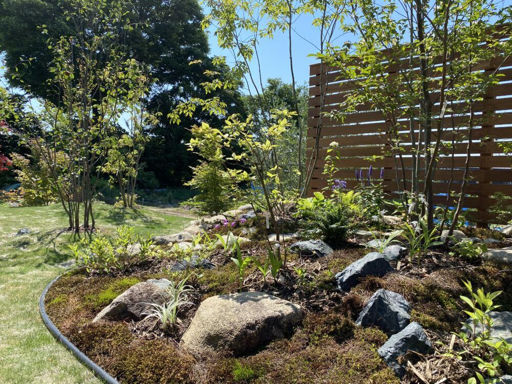 芝生をエッジングし植栽部に芝が入り込むのを防ぎます。  植栽部の奥に入りやすいように飛石を据えてあります。