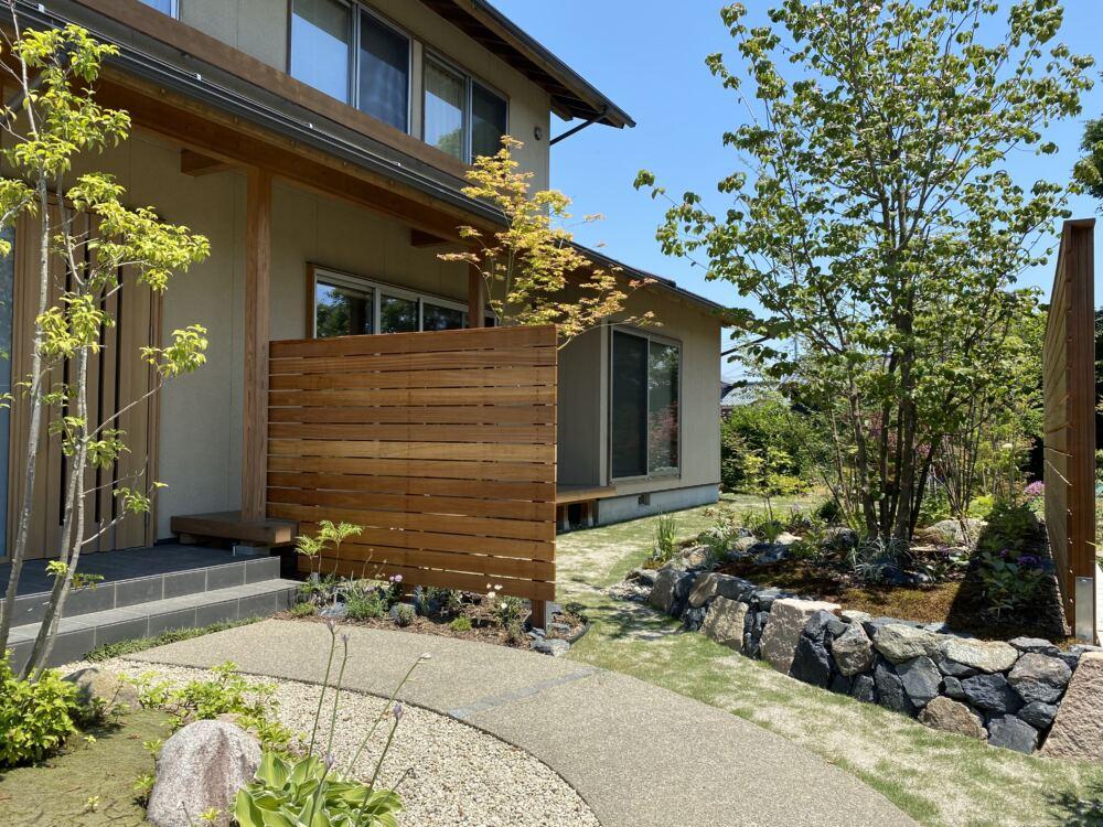 リビングの目隠しとなるフェンスは風合いと経年変化が楽しめるハードウッドを使用しています。 高木のヤマボウシの株立ちが建物を引き立てます。