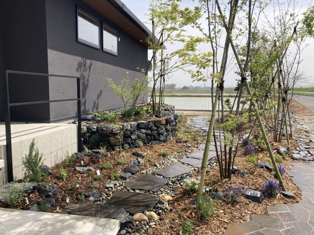 素朴な田園風景に映える植物と石を組み合わせた里山の趣のあるデザイン。 道路側の土留めを兼ねた石積みと建物側の高さのある石積みの間には鉄平石のアプローチ。 高低差のある植栽で一層、モダンな平屋住宅が引き立ちます。 玄関ポーチ前のスタイリッシュな手摺はオーダーメイドしたもの。