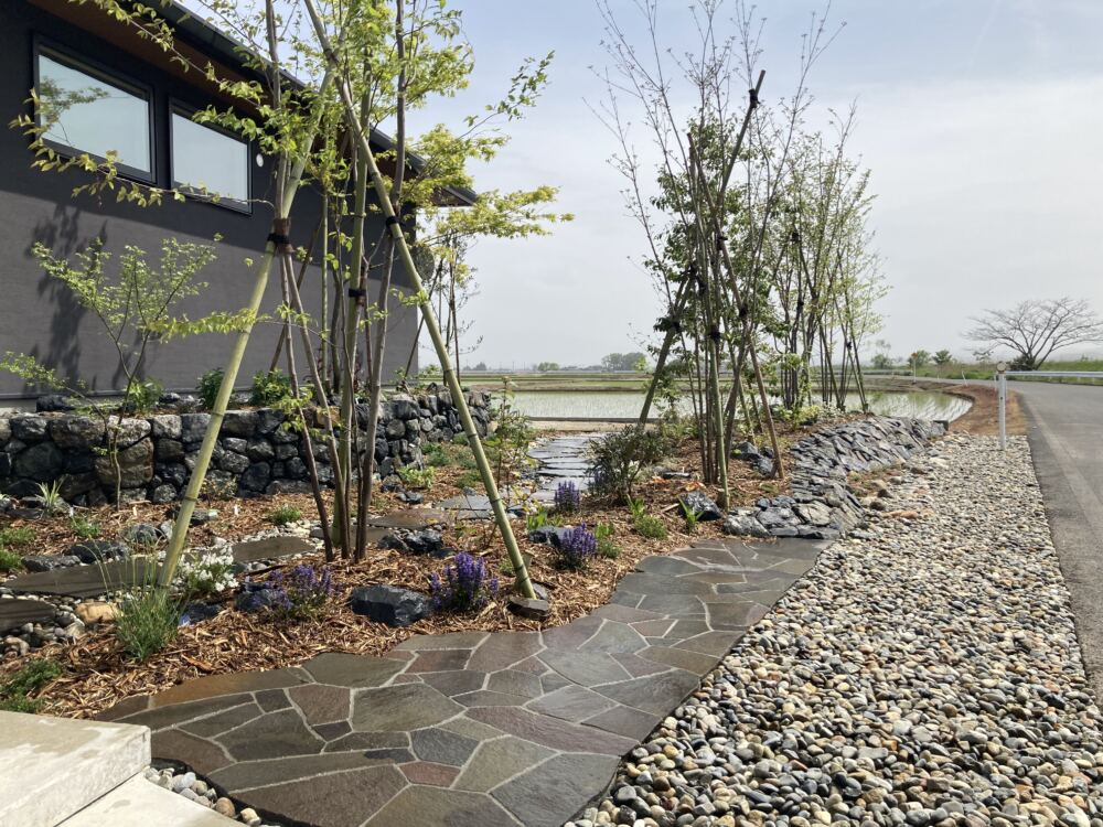 玄関ポーチを降りるとモダンな鉄平石の石張りからなだらかな傾斜の石積みへ。 石の持つ力強さと風に揺れる雑木のしなやかさの対比が美しいお庭です。