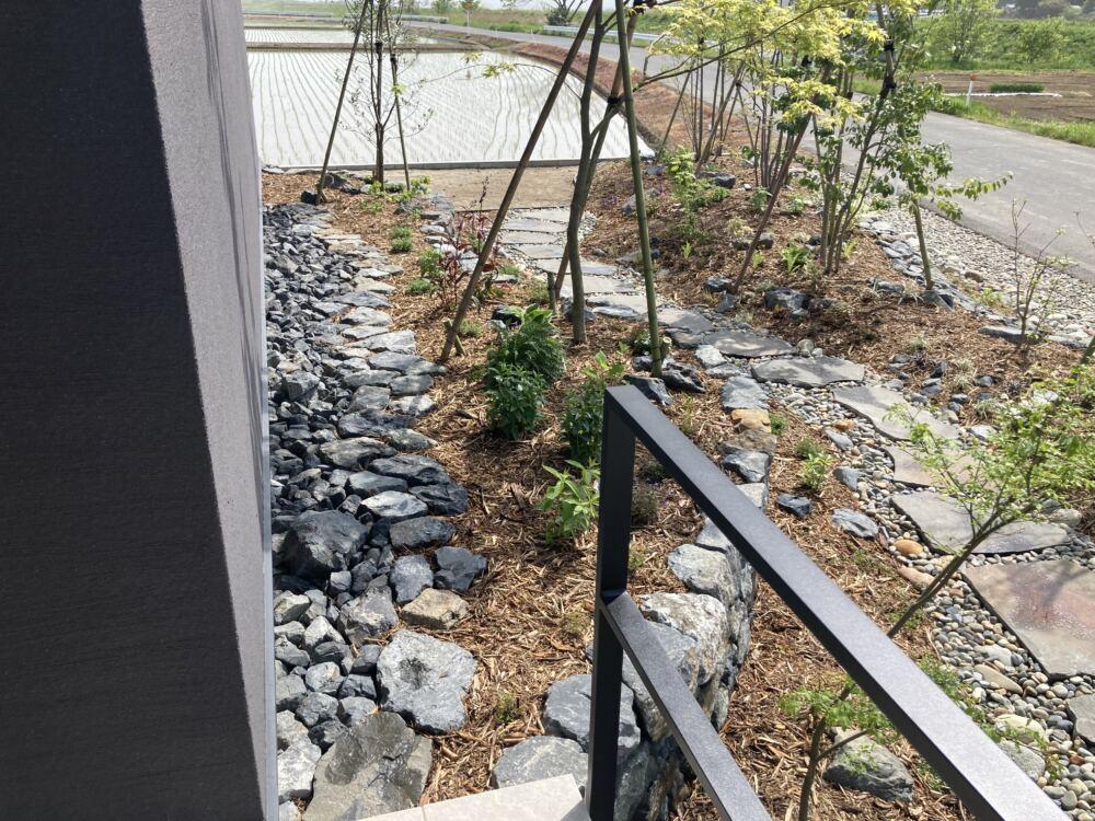 建物側の石積みの植栽部。 雨水の泥ハネで外壁が汚れない様、建物の外壁側は石敷きとなっています。 また、植物のメンテナンスの際は通路としてお使いいただけます。